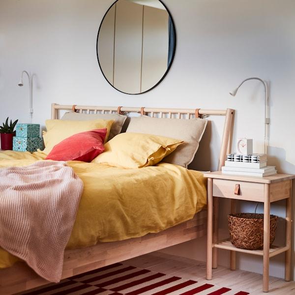 Ein BJÖRKSNÄS Bettgestell und ein Ablagetisch aus Birkenholz mit Lederdetails. Hinzu ein runder Spiegel und gelbe Betttextilien.