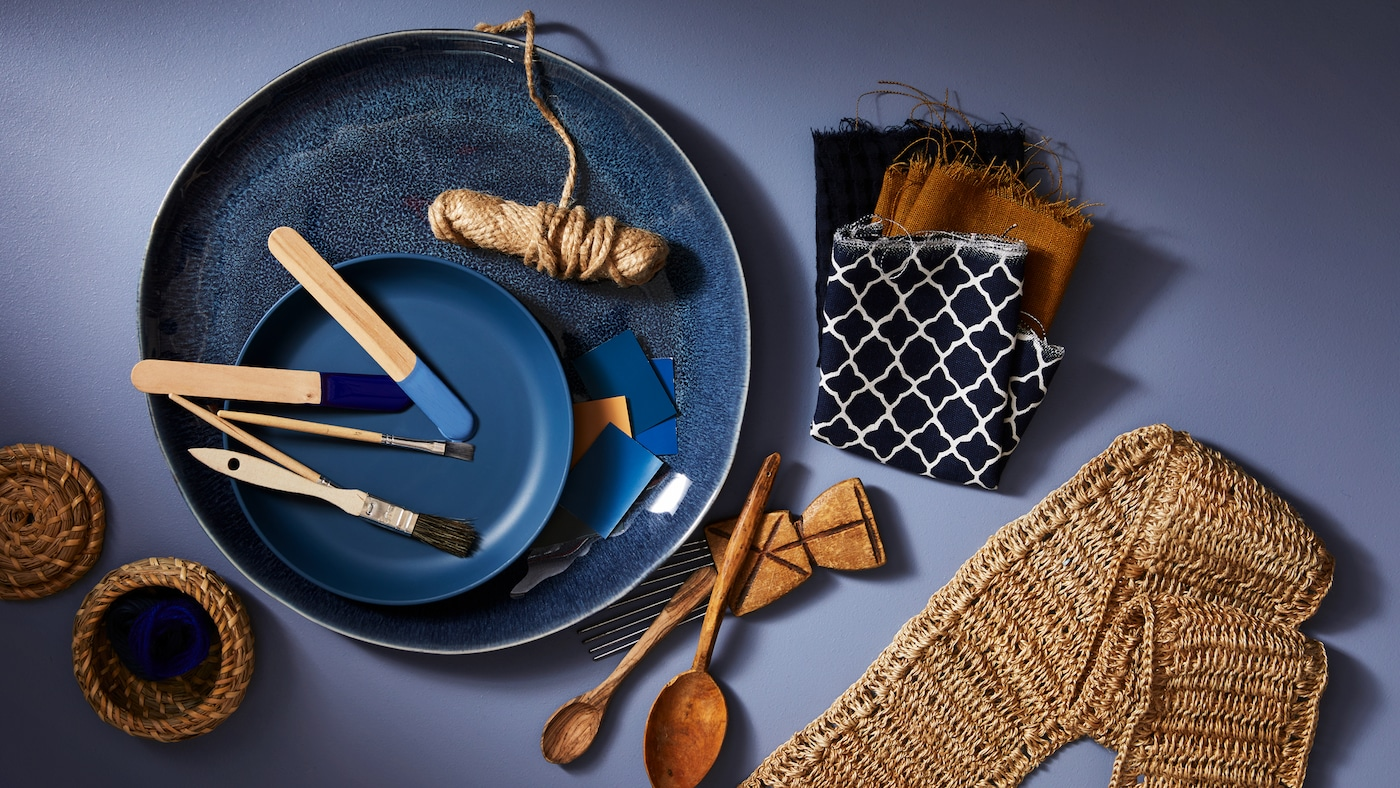 Ein blauer Dessertteller auf einem größeren blauen Teller, auf dem verschiedene Utensilien wie Pinsel und Farbmuster liegen.