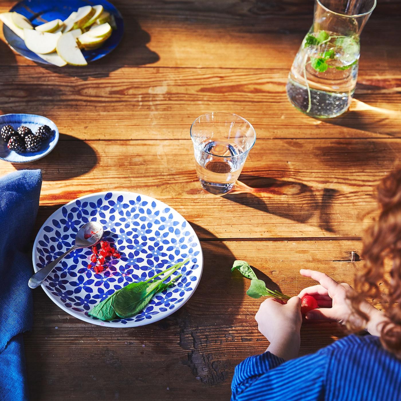 Ein Blick von oben auf eine Person, die ein Radieschen in der Hand hat. Daneben ein MEDLEM Dessertteller weiss/blau/gemustert mit einem Löffel darauf.