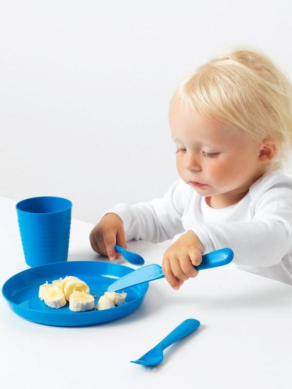 Ein blondes Kind ist von blauem KALAS Plastikgeschirr. Auf dem Teller liegen Bananenscheiben.