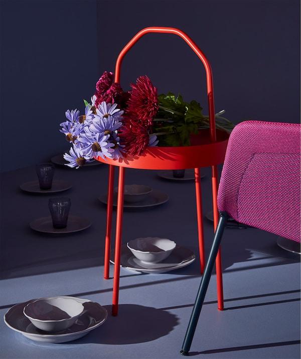 Ein Blumenstrauss bildet den wunderbaren Rahmen für einen BURVIK Ablagetisch in Rot.