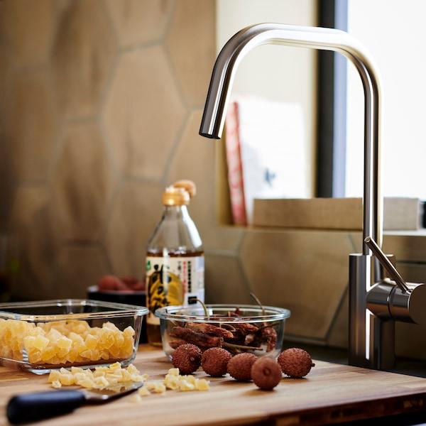 Ein braunes NORRSJÖN Holzschneidebrett mit zwei Glasbehältern unter einer ÄLMAREN Küchenmischbatterie in Edelstahlfarben