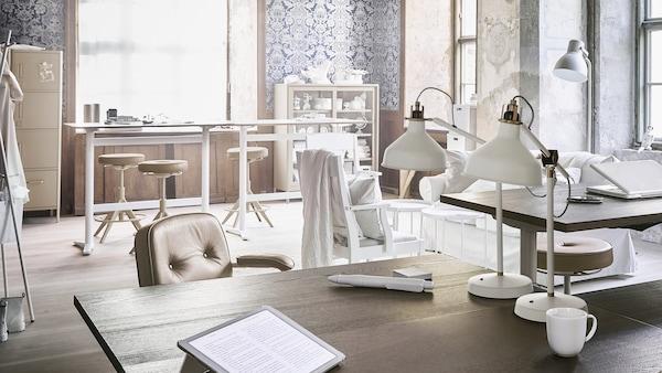 Ein Bürobereich mit verschiedenen Schreibtischen und Sitzgelegenheiten, Tischleuchten, einer Standleuchte und offenen wie geschlossenen Aufbewahrungselementen.