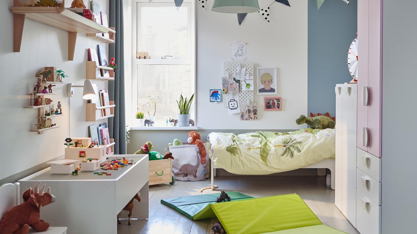 Ein bunt eingerichtetes Spielzimmer und Kinderschlafzimmer in Einem mit einem Kleiderschrank, einem Spieltisch und Stofftierdinosauriern.