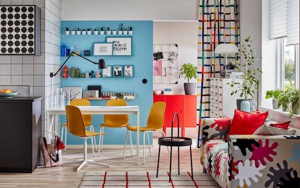 Ein buntes Esszimmer mit weißem Tisch, buntem Sofa, weißem Schubladenelement, schwarzem Beistelltisch und Tischleuchte.