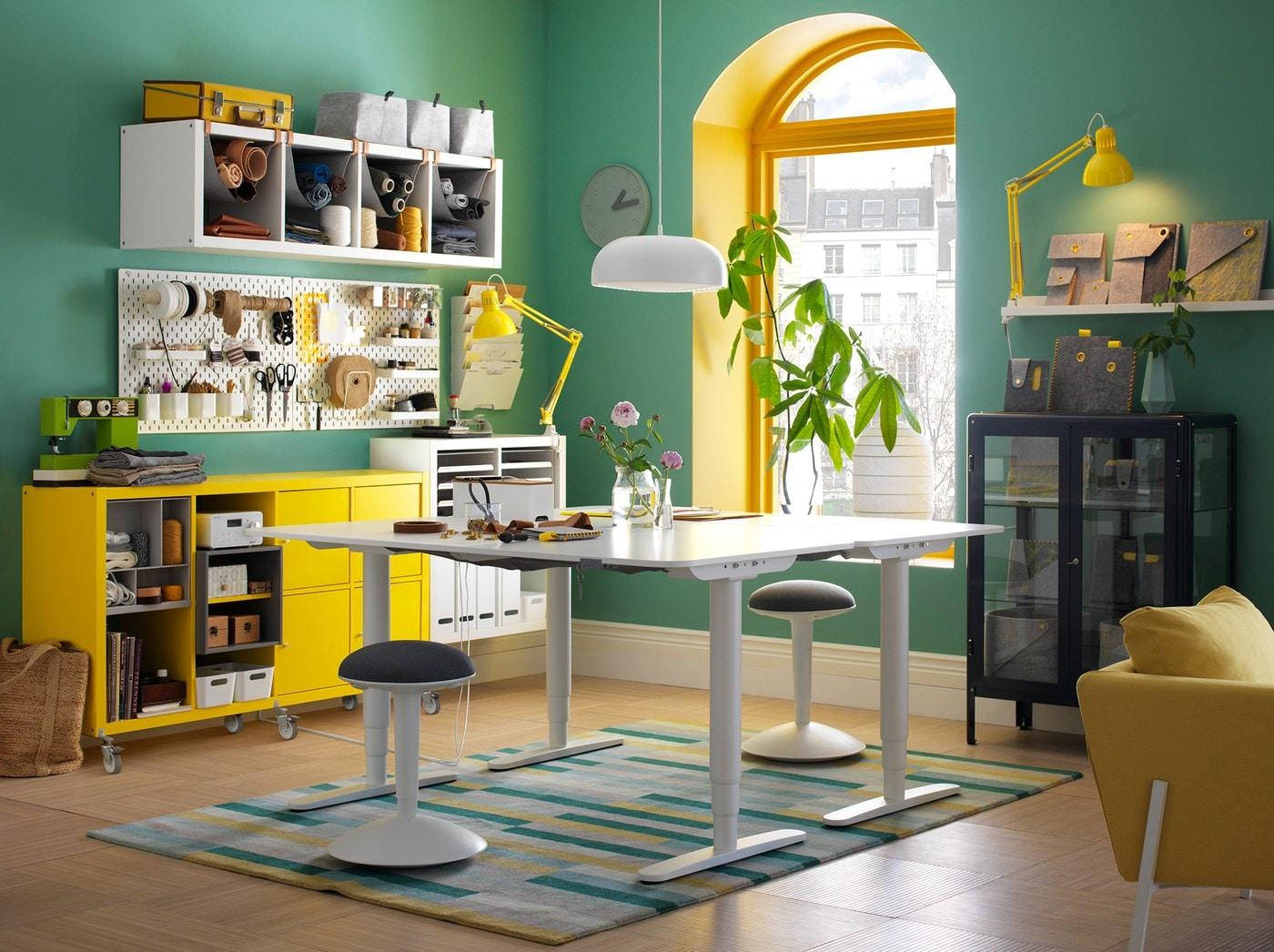 Ein buntes, farbenfrohes Büro in Grün, Weiß und Gelb mit zwei BEKANT Schreibtischen zum Sitzen & Stehen