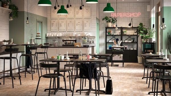 Ein Café mit schwarzen Tischen und Stühlen, grünen und weißen Wänden,  grünen Hängeleuchten, Pflanzen und einem Schreibwarenladen ist zu sehen.