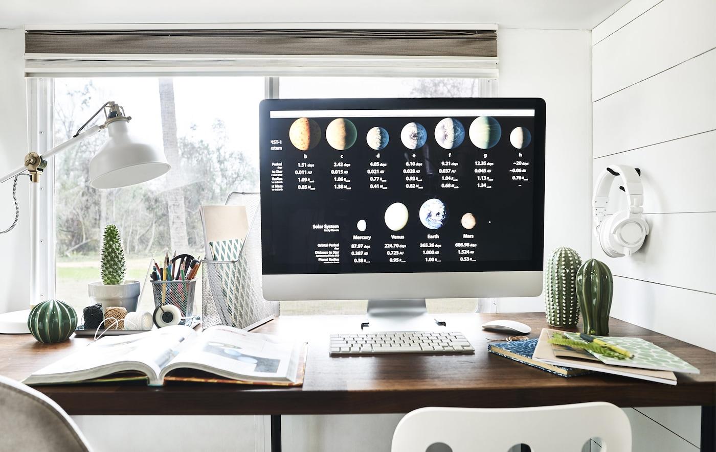 Ein Computermonitor auf einem Schreibtisch, auf dem außerdem Notizblöcke, Ordner und eine Leuchte zu sehen sind.