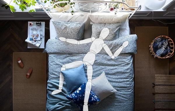 Ein Doppelbett mit Bettwäsche, auf dem die Umrisse einer darauf liegenden Holzfigur sind.