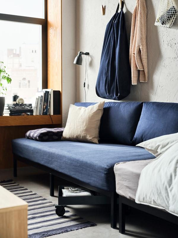 Ein dunkelblaues RÅVAROR Tagesbett steht vor einer Betonwand. Ein RÅVAROR Beutel hängt darüber.