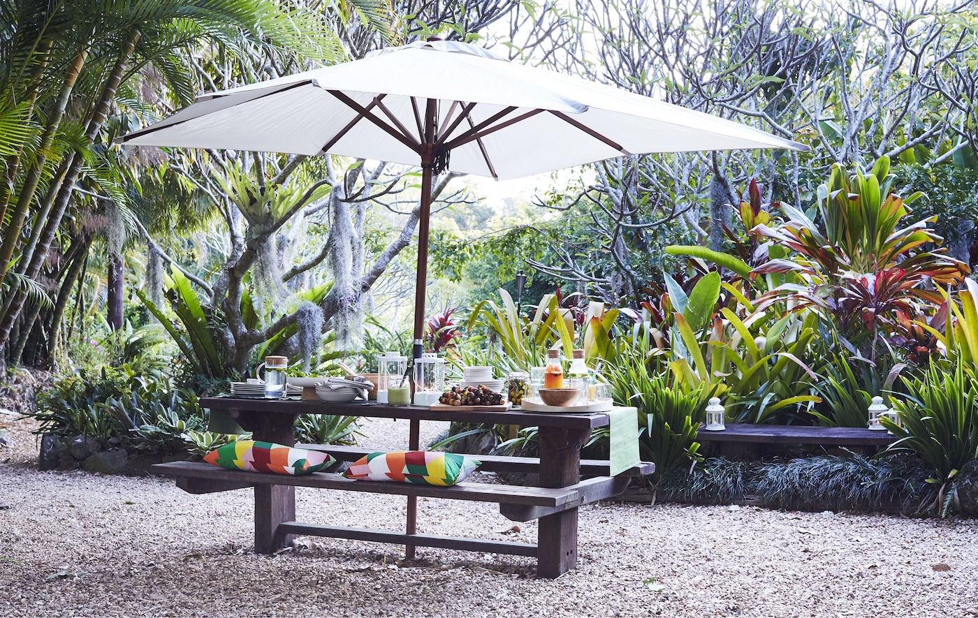 Ein dunkelbrauner, gedeckter Holztisch mit Bank & Sonnenschirm in einem Tropengarten