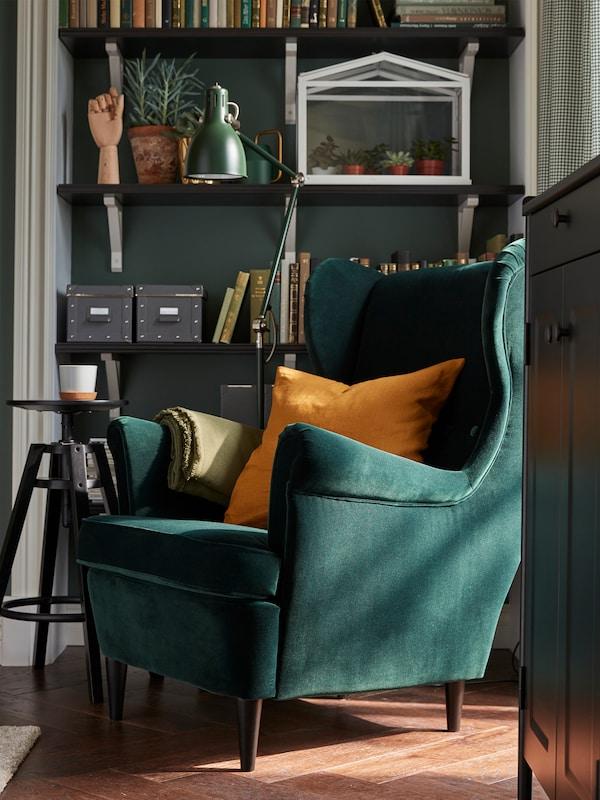 Ein dunkelgrüner STRANDMON Ohrensessel mit einem Kissen und umgeben von einem Hocker, einer Standleuchte und einem Bücherregal.
