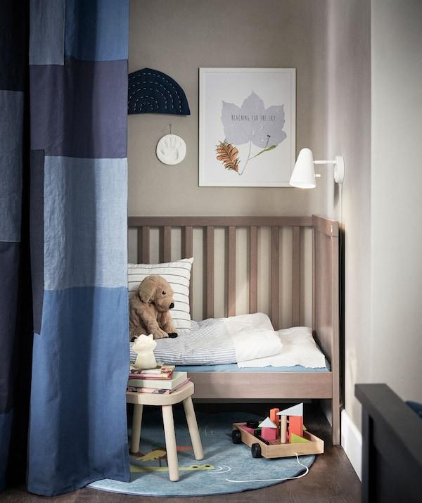 Ein durch eine Gardine abgetrennter Bereich mit einem SUNDVIK Babybett, in dessen Umgebung Stofftiere und Bilderbücher zu sehen sind.