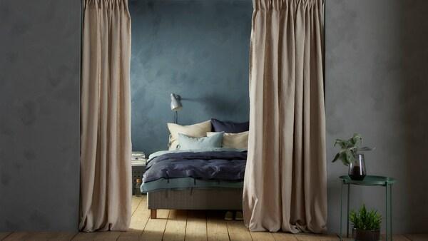 Ein Durchgang in ein Schlafzimmer mit geöffneten AINA Gardinenschals davor.