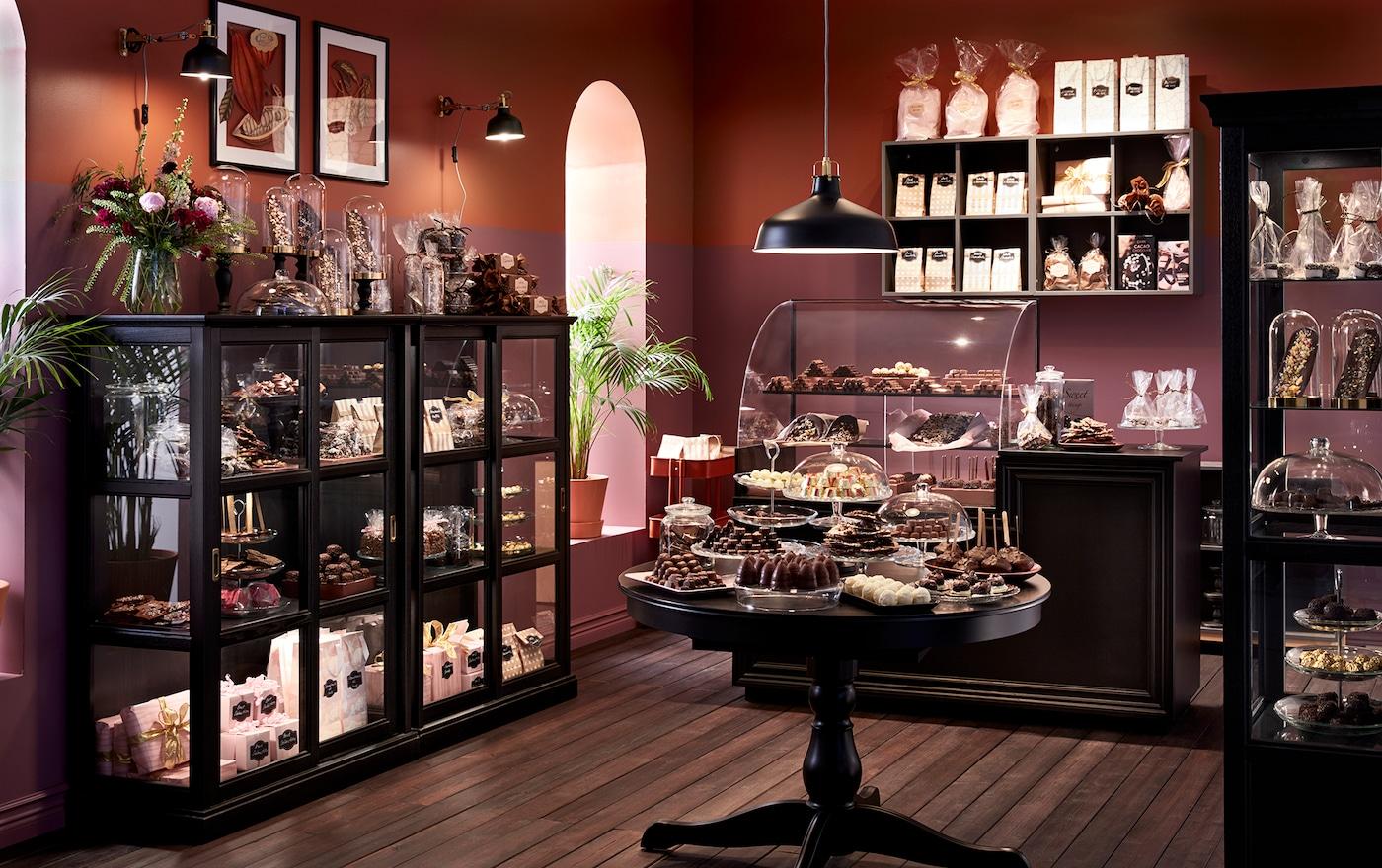 Ein edles Schokoladengeschäft mit schwarzen MALSJÖ Vitrinen, einem INGATORP Tisch & tollen Accessoires