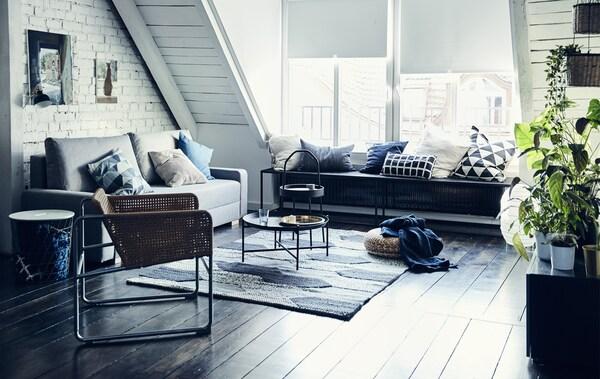 Ein einfarbig gehaltenes Wohnzimmer mit Dachschräge, einem grauen Sofa, einem Rattansessel und einem großen Teppich
