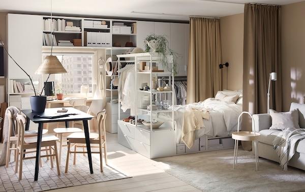 Ein Einzimmerapartment, u. a. mit einem PLATSA Bettgestell mit 4 Schubladen in Weiß, einem Esstisch, einem grauen Sofa und beigefarbenen Gardinen.