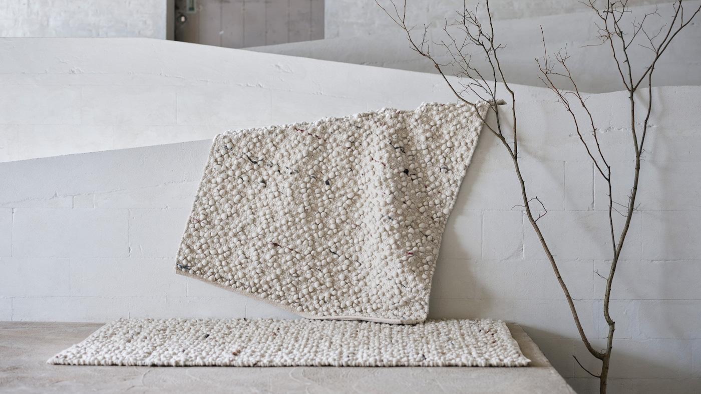 Ein elfenbeinweißer SVÄRDBORG Teppich mit eingewebten bunten Noppen ist über eine weiße Wand drapiert; davor liegt ein weiterer SVÄRDBORG Teppich.