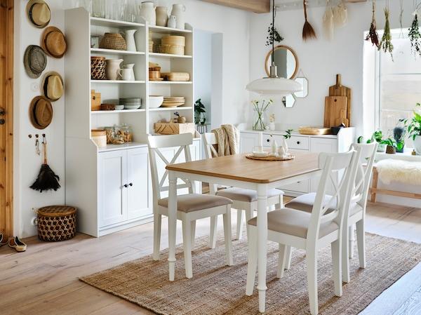 Ein Essbereich mit einem Esstisch in Eiche/Weiß, vier weißen Stühlen, einem Juteteppich und zwei weißen Hochschränken mit jeweils zwei Türen