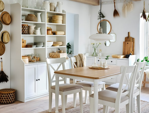 Ein Essbereich mit einem Tisch und Stühlen und offenen HAUGA Kleiderschränken mit 3 Schubladen in Weiß und einer weißen HAUGA Kommode an den Wänden