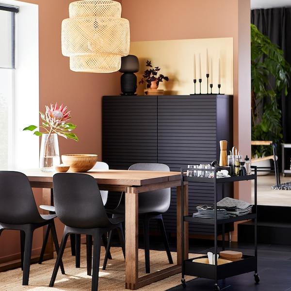 Ein Essplatz mit schwarzen Stühlen und einem Esstisch aus Holz. Im Hintergrund steht ein schwarzer Schrank mit Lamellentüren.