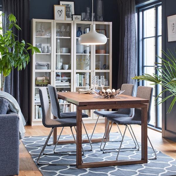 Ein Esstisch aus Holz in einem Graublau eingerichteten Esszimmer. Über dem Tisch ist eine Hängeleuchte, an der Rückwand dahinter sind zwei Regale mit Glastüren zu sehen.