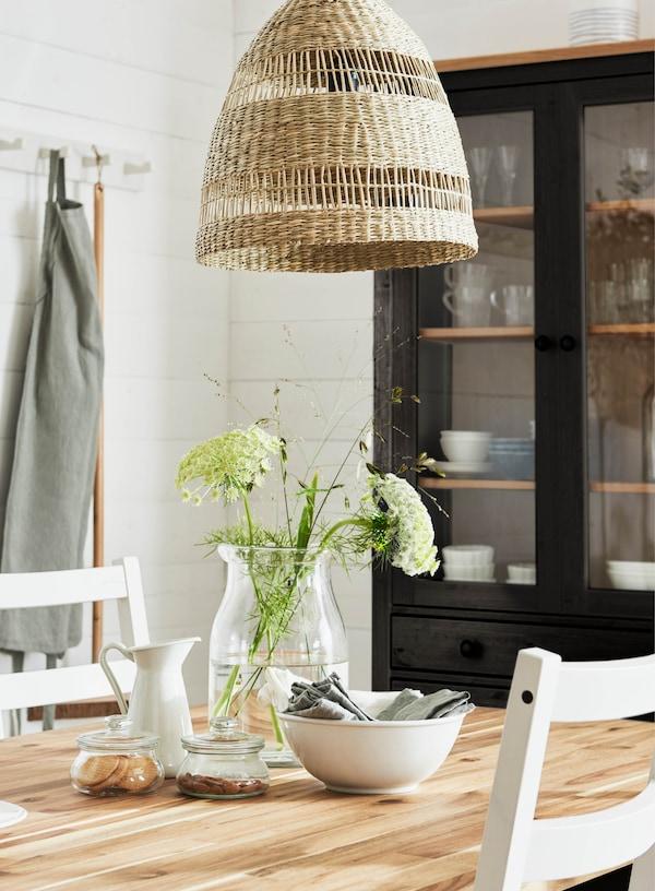 Ein Esstisch aus Holz mit einer Galsvase und frischen Blumen unter einer Lampe aus Seegras.