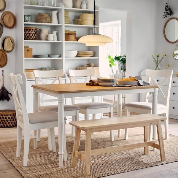 Ein Esstisch in Eiche/Weiß, vier weiße Stühle und eine Bank in Birke stehen auf einem Juteteppich. Im Hintergrund sind zwei Hochschränke zu sehen.