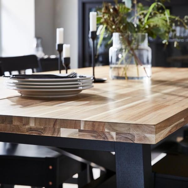 Ein Esstisch mit einer dicken Tischplatte, Unterbau und Beine in Schwarz.