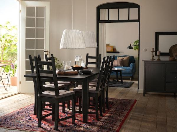 Ein Esszimmer in Braun und Cremefarben u. a. mit einem Tisch im traditionellen Look und KAUSTBY Stühlen in Schwarzbraun auf einem roten Perserteppich