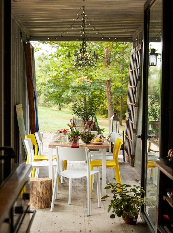 Ein Esszimmer mit Öffnung zum Garten, u. a. mit JANINGE Stuhl weiss