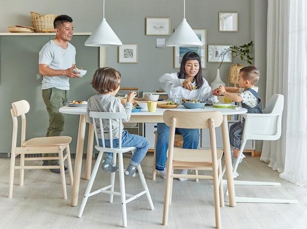 Ein familienfreundliches Esszimmer mit mehreren RÖNNINGE Stühlen, weißem Tisch, weißem Regal und Bildern an der Wand. Mutter und die Kinder sitzen am Tisch, der Vater steht.