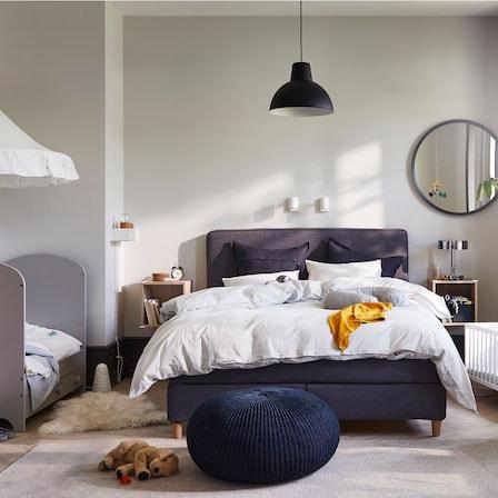 Ein familienfreundliches Schlafzimmer mit Babybett, Wiege, dunkelgrauem Boxspringbett, Babydecke, Tischleuchte und Bettwäsche.