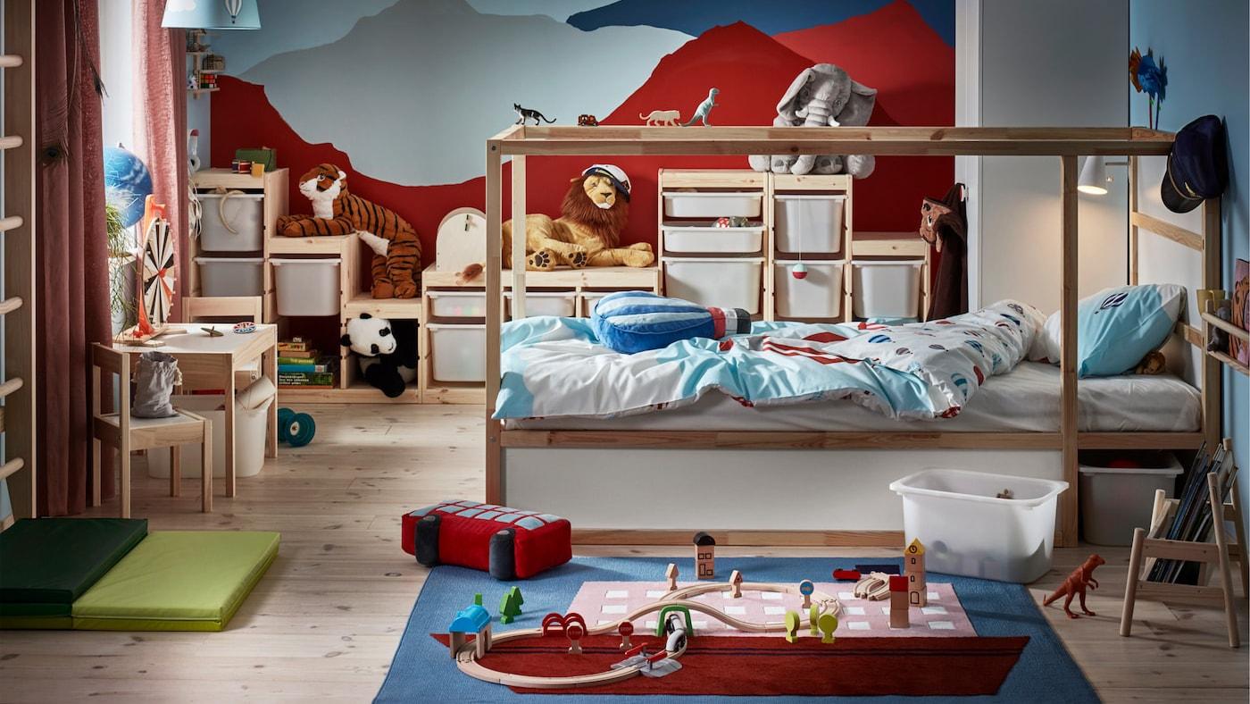 Ein fantasievolles Kinderzimmer mit weißem Bett, Regalkombi, Kindertisch, weißem Kleiderschrank, Leuchtenschirm und Spielzeug.