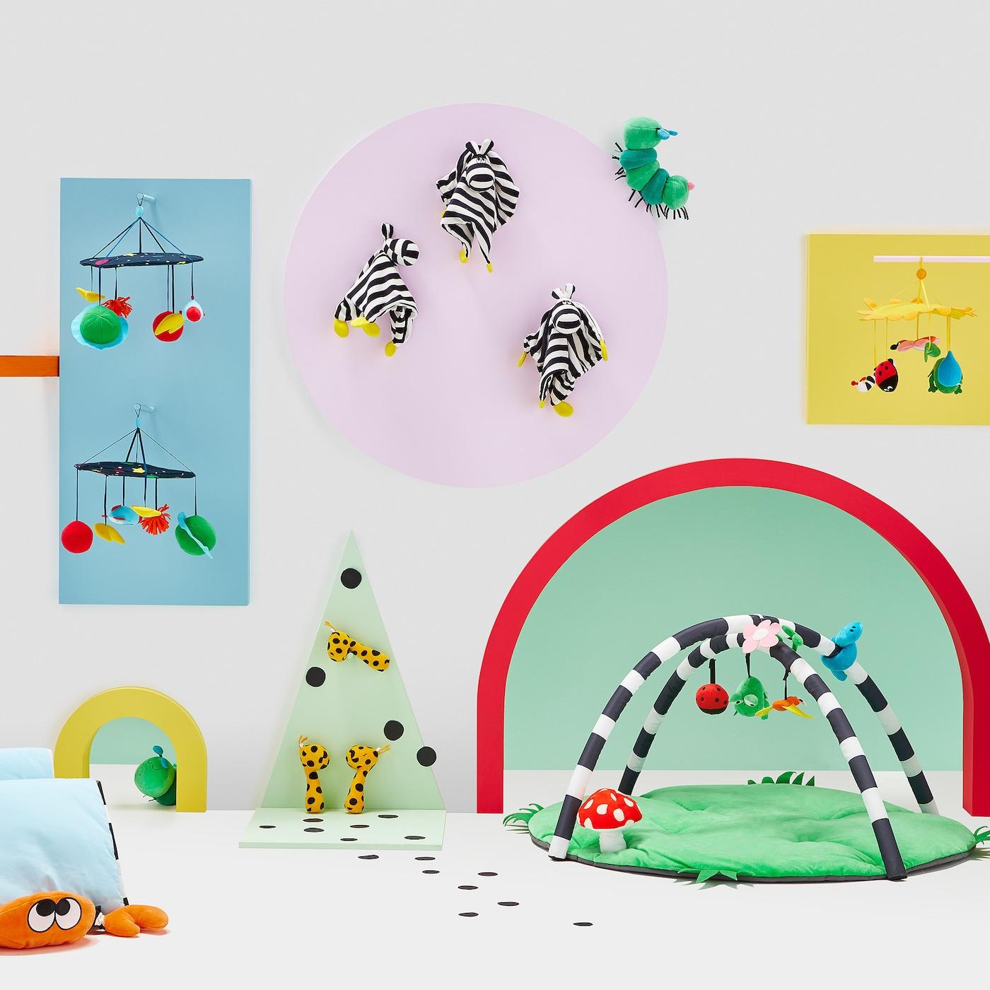 Ein farbenfrohes Babyzimmer mit buntem Babyspielzeug wie Mobile, Kuscheltiere & mehr.