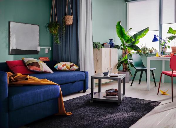 Ein farbenfrohes und einladendes Wohnzimmer, mit einem blauen Schlafsofa und bunten Kissen. Daneben steht ein grüner und ein roter Stuhl gepaart mit einem weißen Tisch vor einem Fenster.