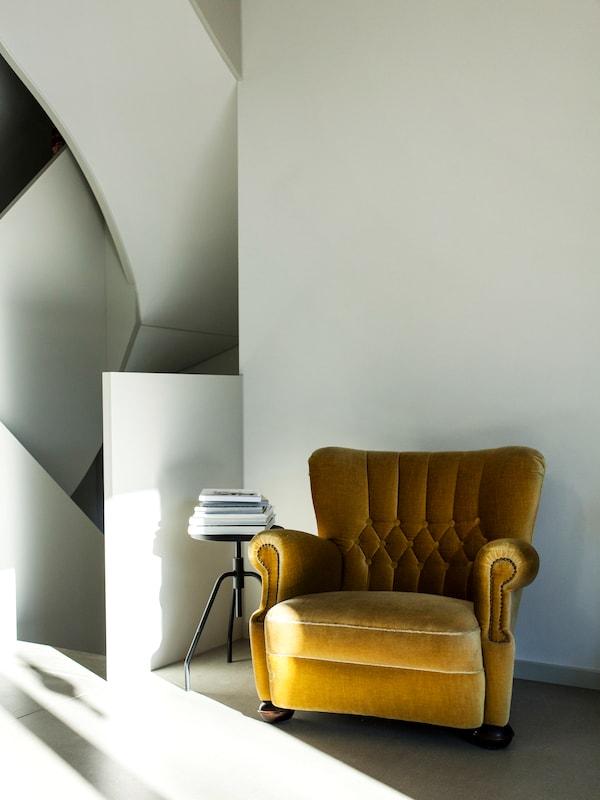 Ein farbiger Sessel sorgt in einem schlichten Zuhause für Abwechslung.