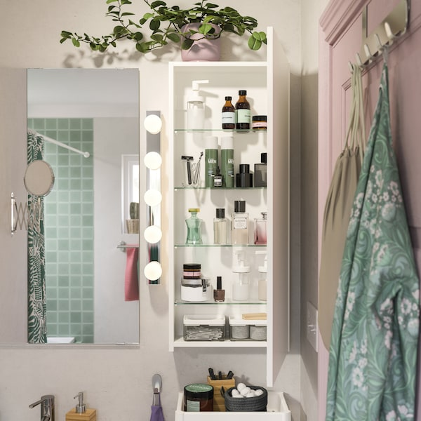 Ein flacher GODMORGON Wandschrank mit geöffneter Tür ist hier neben dem Badezimmerspiegel zu sehen. Auf den Böden im Schrank sind Parfümflaschen, Cremes und weitere Badutensilien aufbewahrt.