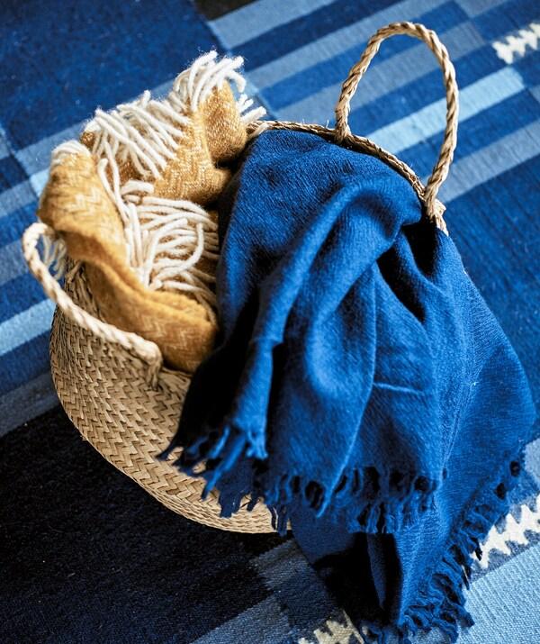 Ein FLÅDIS Faltkorb auf einem TRANGET Teppich in Blautönen