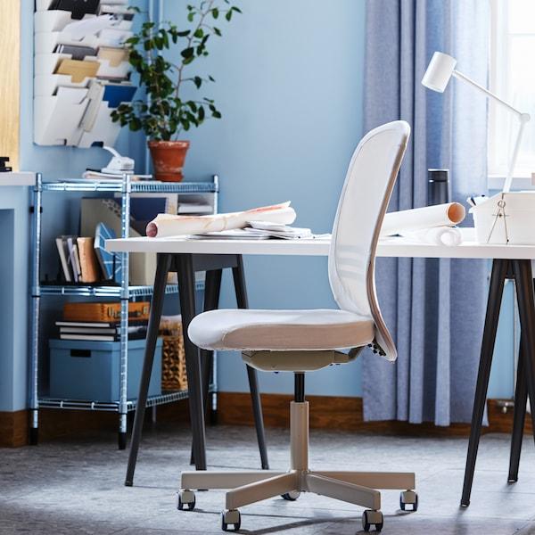 Ein FLINTAN Drehstuhl steht in einem blauen Büro neben einem weissen Schreibtisch und einem OMAR Regal, in dem sich Unterlagen und Kästen befinden.