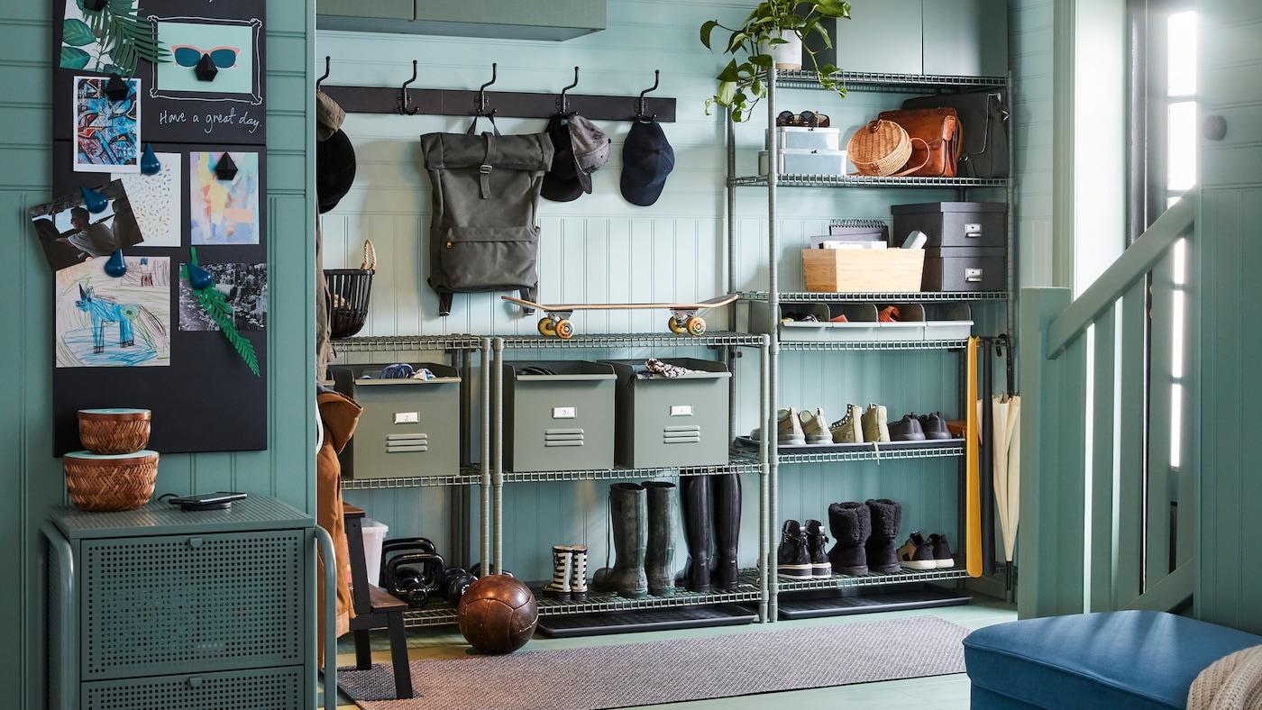 Ein Flur mit dem OMAR Regal mit Schuhen, Stiefeln und den REJSA Boxen aus Metall. Dazu an der Wand zwei PINNIG Hakenleisten an der Wand.