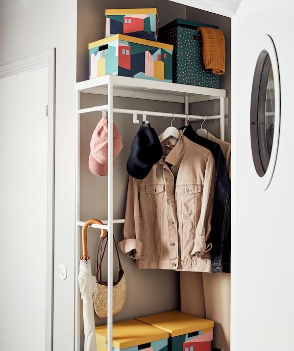 Ein Flur mit einem MACKAPÄR Garderobenständer, an dem Jacken und Accessoires hängen bzw. in dem verschiedene TJENA Kästen stehen
