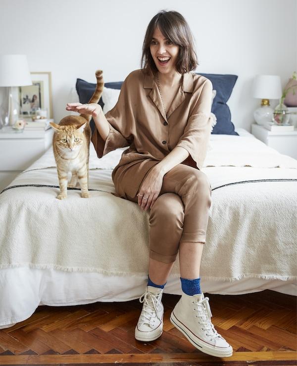 Ein Foto von Carolina und ihrer Katze auf dem Bett