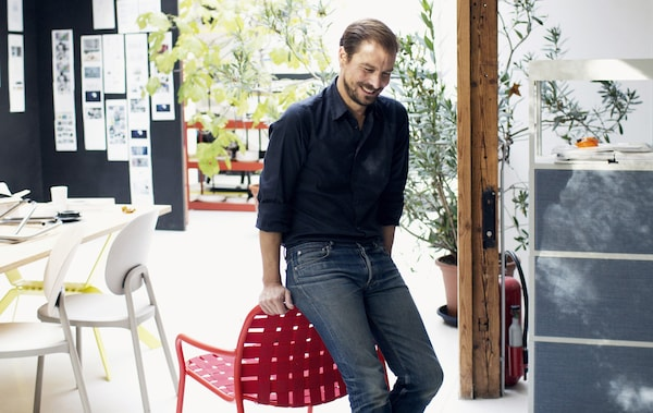 Ein Foto von Designer Stefan Diez angelehnt an einem roten Stuhl in einem Büro