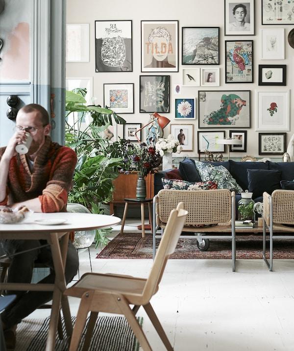 Ein Foto von Łukasz am Esstisch, u. a. mit SLÄHULT Tischplatte in Weiss. Er trinkt aus einem Becher. Hinter ihm öffnet sich der Blick auf das Wohnzimmer mit einer Galeriewand.
