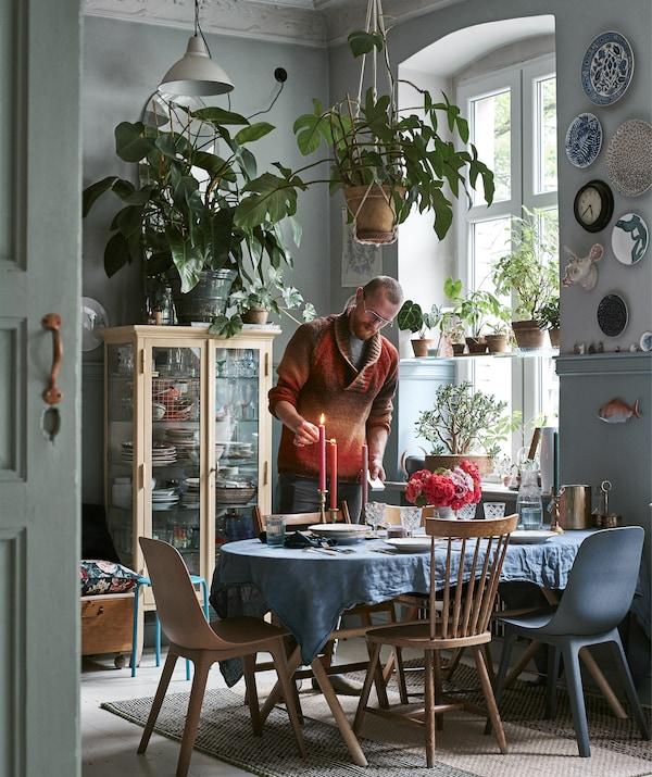 Ein Foto zeigt Łukasz, wie er auf einem gedeckten Tisch Kerzen anzündet.