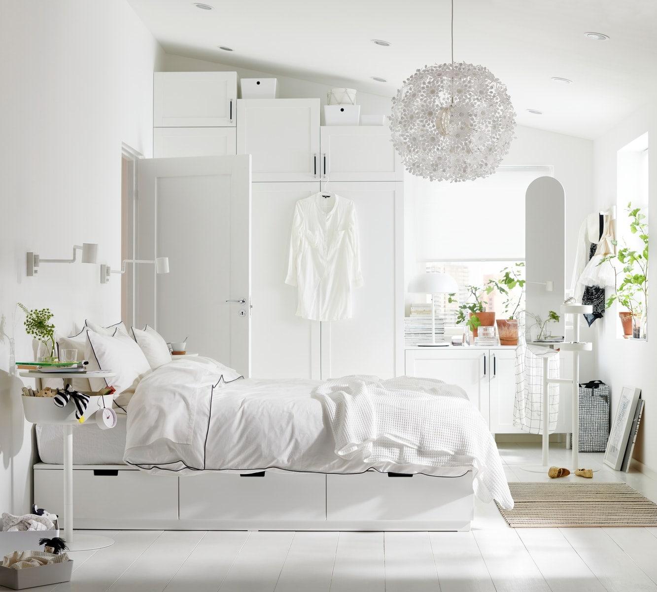 Ein freundliches, weißes Schlafzimmer mit einem weißen Kleiderschrank, Kleiderständer und Wandleuchte.