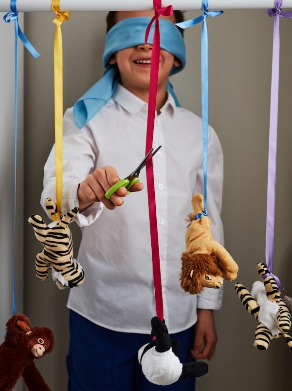 Ein fröhliches Kind mit Augenbinde steht vor einer Reihe hängender DJUNGELSKOG Stofftiere, die an Bändern hängen, und versucht eines davon mit einer MÅLA Schere abzuschneiden.