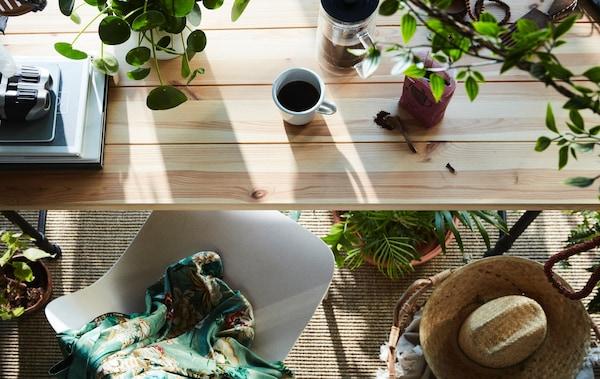 Ein Frühstückstisch mit jeder Menge echten und künstlichen Pflanzen, u. a. FEJKA Topfpflanze, künstlich drinnen/draußen/hängend.