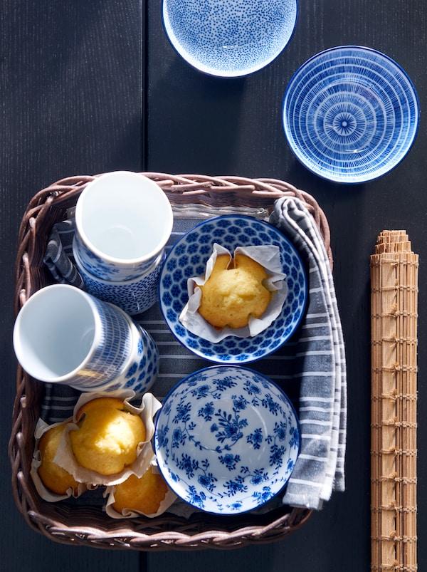 Ein GABBIG Korb, der mit einem TIMVISARE Geschirrhandtuch ausgeschlagen ist und in dem ENTUSIASM Becher und frisch gebackene Muffins liegen